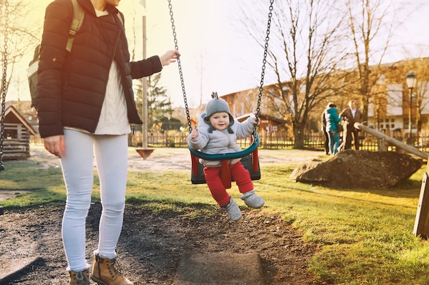 Matka z dzieckiem ubrana w ciepłe ubrania spacerująca w słoneczny dzień na świeżym powietrzu
