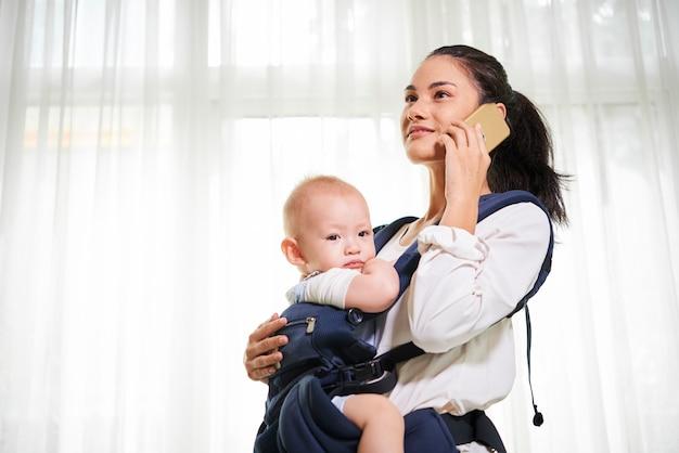 Matka z dzieckiem w chuście w domu