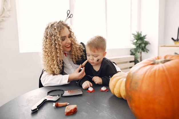 Matka z dzieckiem w kostiumach i makijażu. rodzina przygotowuje się do świętowania halloween.