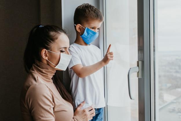 Matka z dzieckiem w maskach medycznych siedzi w kwarantannie w domu i wygląda przez okno. zapobieganie koronawirusowi i covid -19
