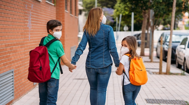 Matka z dziećmi chodzi do szkoły z maskami