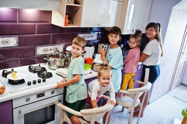 Matka z dziećmi gotuje w kuchni, szczęśliwe chwile dzieci.