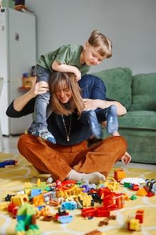 Matka z dziećmi obejmując, bawiąc się, śmiejąc się w domu. rodzic z synami spędzającymi razem czas