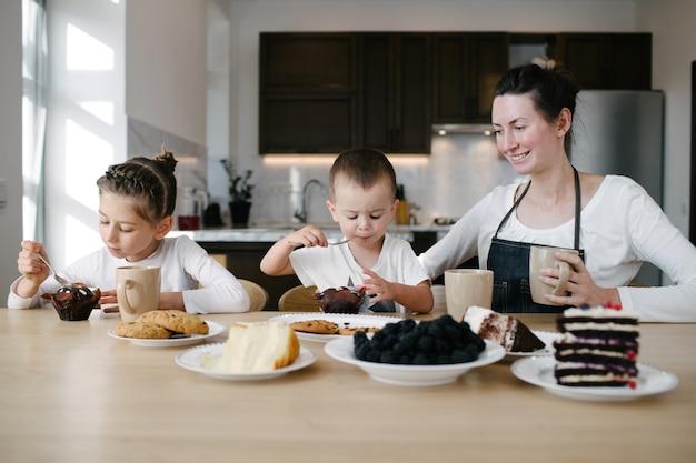 Matka z dziećmi pije gorącą czekoladę i latte w domowej kuchni. są uśmiechnięci i dobrze się bawią. pojęcie macierzyństwa