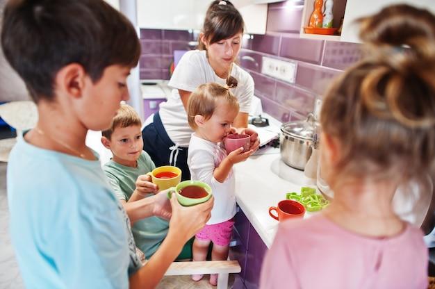 Matka z dziećmi pije kompot w kuchni, szczęśliwe chwile dzieci.