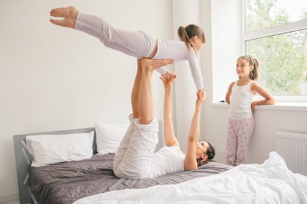 Matka z dziećmi robi joga ćwiczeniu w łóżku
