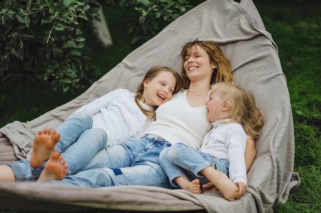 Matka z dziećmi zabawy w hamaku. mama i dzieciaki w hamaku.