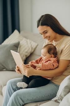 Matka z dziewczyną bbay używa tabletu w domu