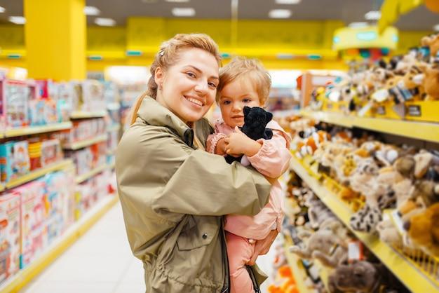 Matka z dziewczyną wybiera pluszowego psa w sklepie dla dzieci