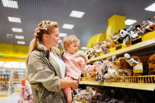 Matka z dziewczyną wybiera zabawki w sklepie dla dzieci