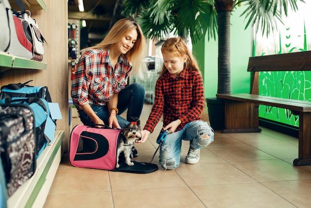 Matka z dziewczyną wybierając torbę dla małego szczeniaka w sklepie zoologicznym. kobieta i małe dziecko kupują sprzęt w sklepie zoologicznym, akcesoria dla zwierząt domowych
