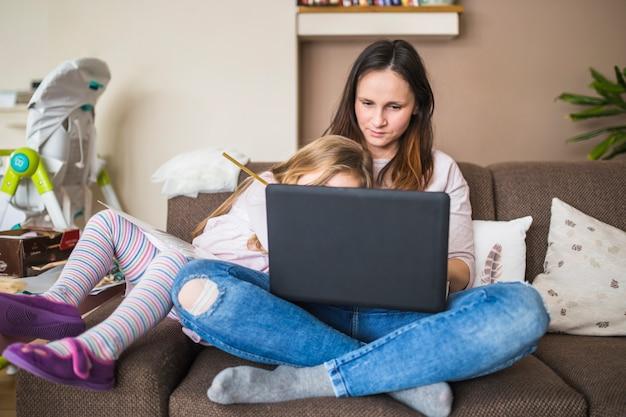 Matka z jej córki obsiadaniem na kanapie używać laptop