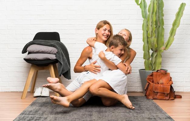 Matka z jej dwa dziećmi przy indoors ściskać