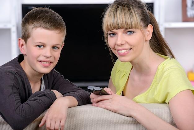 Matka z jej młodym synem ogląda telewizję wpólnie.