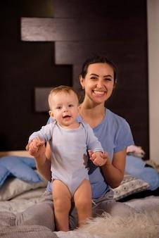 Matka z jej ślicznym synkiem bawić się na łóżku.