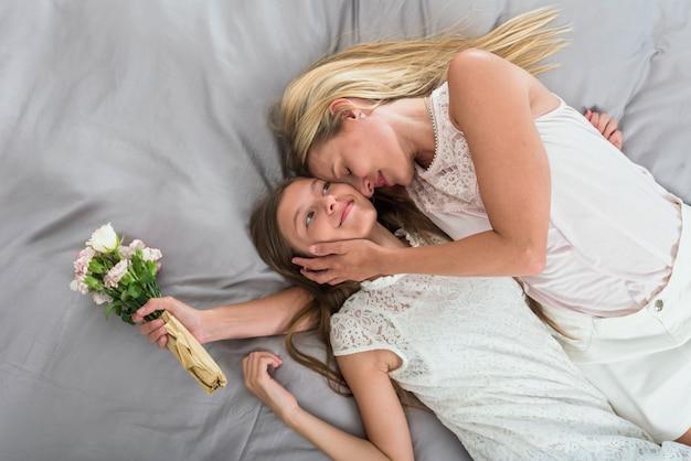 Matka z kwiatami ściska córkę na łóżku