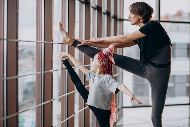Matka z małą córeczką ćwiczącą jogę przy oknie