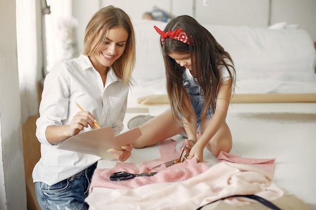 Matka z małą córeczką mierzy materiał do szycia