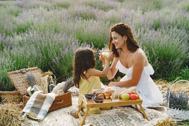 Matka z małą córeczką na lawendowym polu. piękna kobieta i słodkie dziecko grając w pole łąka. rodzina na pikniku.