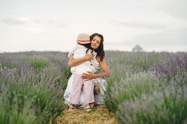 Matka z małą córeczką na lawendowym polu. piękna kobieta i słodkie dziecko grając w pole łąka. urlop rodzinny w letni dzień.