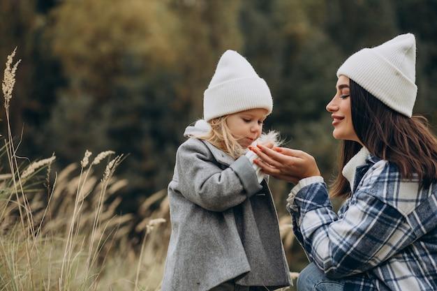 Matka z małą córeczką razem w jesiennej pogodzie bawią się