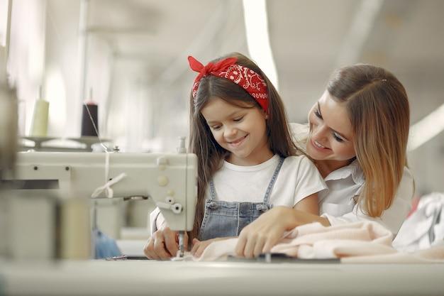 Matka z małą córeczką szyje ubrania w fabryce