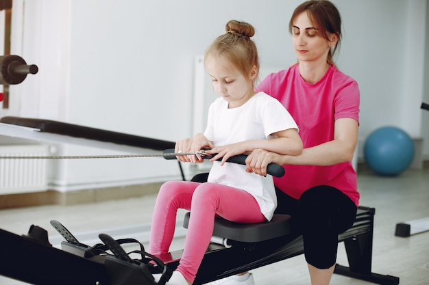 Matka z małą córeczką uprawia gimnastykę na siłowni
