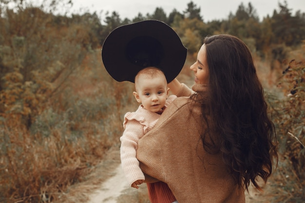 Matka z małą córką bawić się w jesieni polu