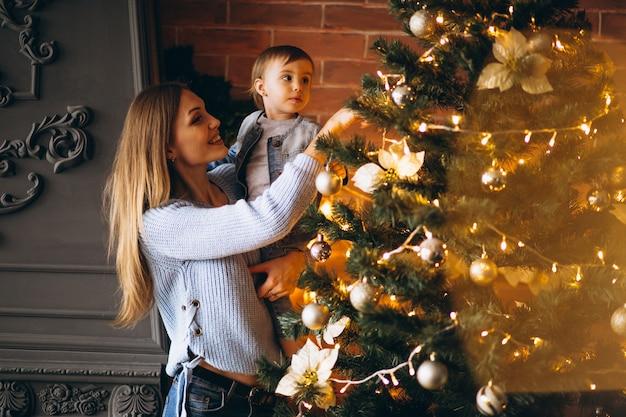 Matka z małą córką dekoruje choinki