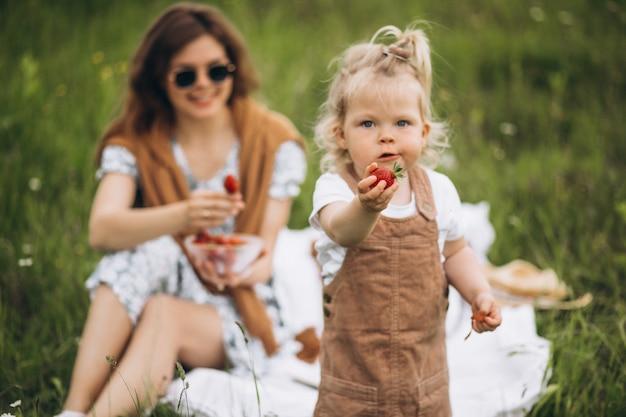 Matka z małą córką ma pinkin w parku