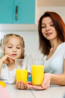 Matka z małą dziewczynką pije sok pomarańczowy podczas wspólnego śniadania