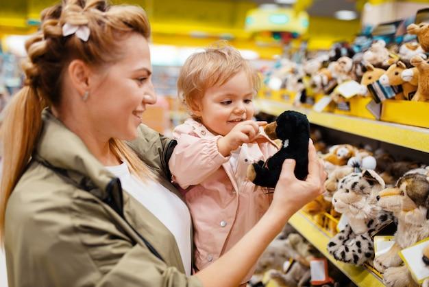 Matka z małą dziewczynką wybiera pluszowego psa w sklepie dla dzieci.