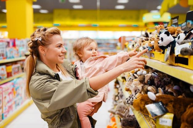 Matka z małą dziewczynką wybiera zabawki w sklepie dla dzieci.