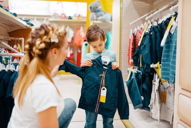 Matka z małym chłopcem wybiera ubrania w sklepie dla dzieci.