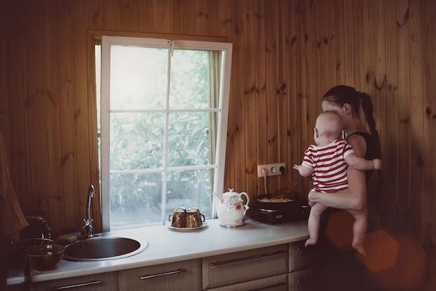 Matka z małym dzieckiem w ramionach gotuje obiad. wnętrze wiejskiego domu