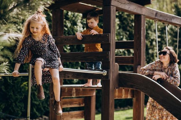 Matka z małym synem i córką ma zabawę w podwórku