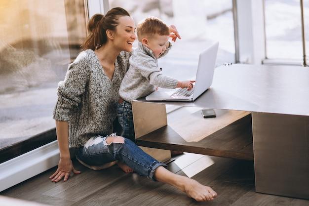 Matka z małym synem pracuje na komputerze w domu