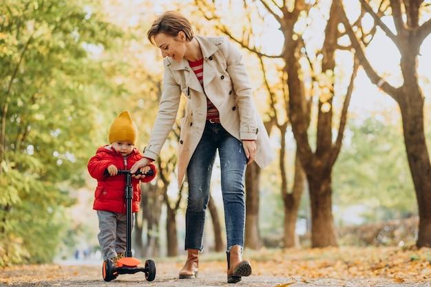 Matka z małym synkiem na skuterze w jesiennym parku