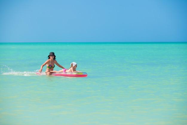 Matka z młodą córką na lotniczym materacu w morzu