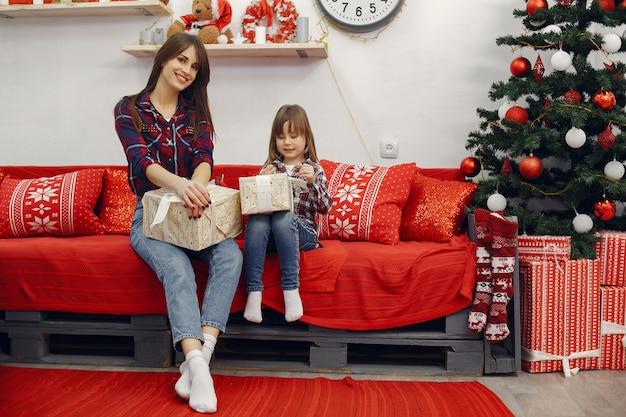 Matka z śliczną córką w domu z boże narodzenie prezentami