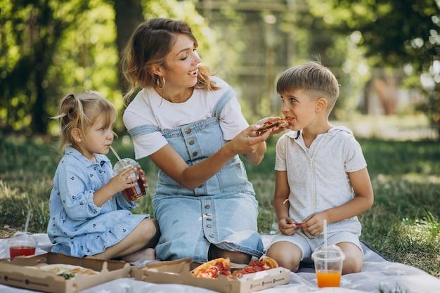 Matka z synem i córką, jedzenie pizzy w parku