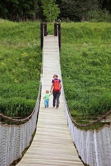 Matka z synem malucha chodzić na most wiszący. koncepcja podróży przygodowej