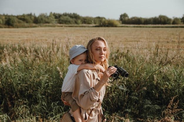 Matka z synem na plecach spaceruje na łonie natury trzymając w rękach lornetkę