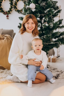 Matka z synem siedzi pod choinką