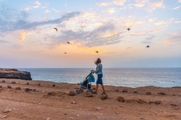 Matka z synem spacerująca po west coast photo point w miejscowości el cotillo na północy wyspy fuerteventura na wyspach kanaryjskich. hiszpania