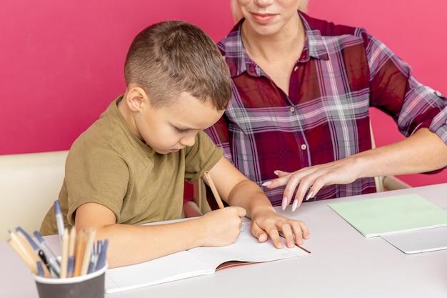 Matka z synem w domu odrabiania lekcji razem w czasie kwarantanny.
