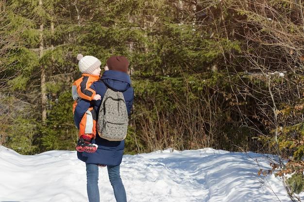 Matka z synem w ramionach i plecaku stoi na tle lasu iglastego i zaśnieżonej drogi. widok z tyłu. zimowy dzień, zbliżenie