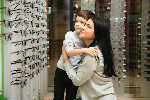 Matka z synem wybierając okulary w sklepie optycznym.
