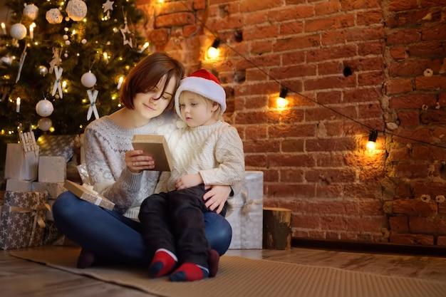 Matka z synkiem, czytając magiczną książkę w przytulnym salonie. czas rodzinny na święta