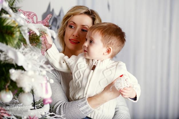 Matka z synkiem ozdabia choinkę